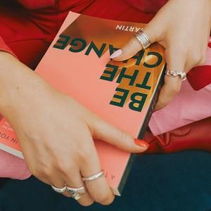 """Frau, die ein Buch mit """"Be the change"""" auf dem Cover hält"""